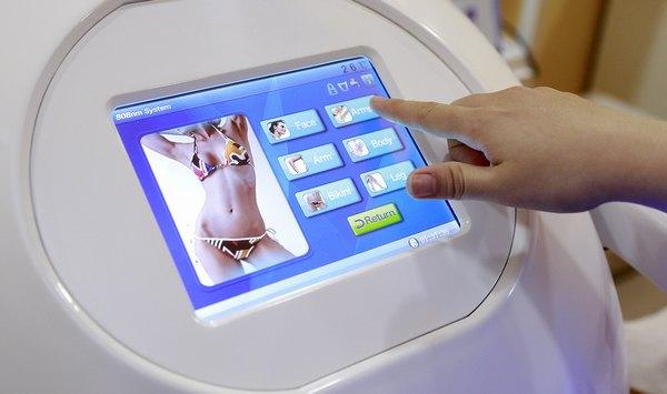 Chuyên viên Thu Cúc điều chỉnh thiết bị để thực hiện triệt lông cho khách hàng