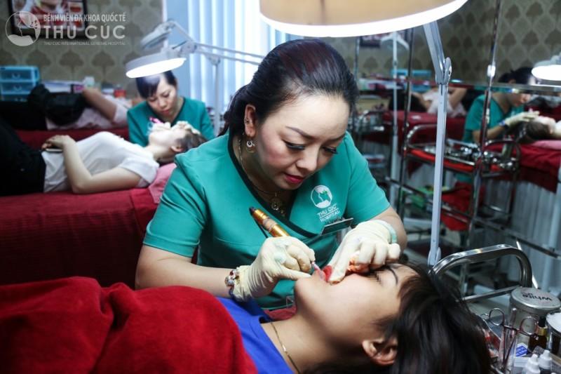 Kỹ thuật viên phun xăm đang thực hiện phun môi cho khách hàng